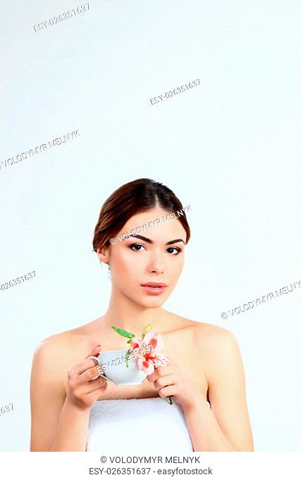 The attractive brunette beautiful girl with cup of herbal tea on white background, youth and skin care concept