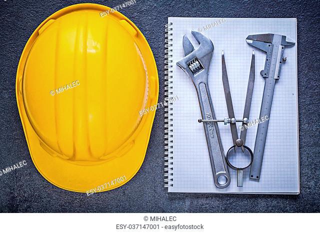 Notebook building helmet adjustable wrench divider calliper on black background