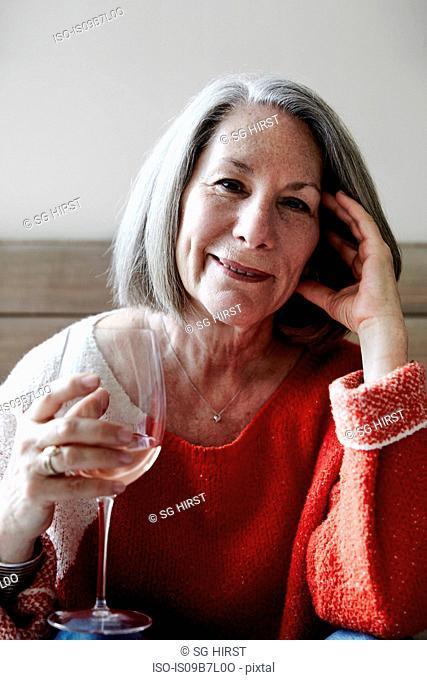 Portrait of senior woman with grey bob sitting on sofa holding glass of rose wine