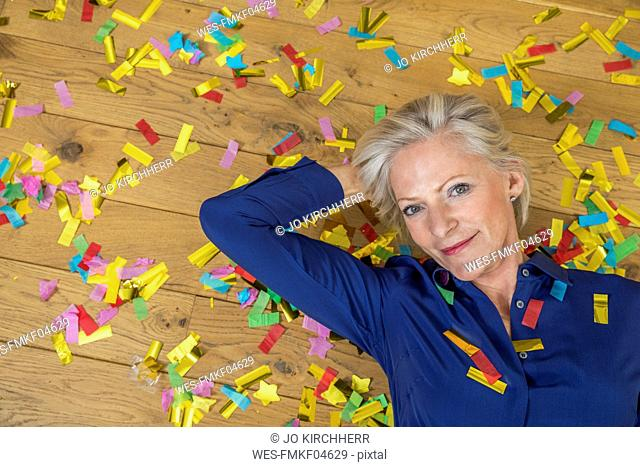 Portrait of smiling senior woman lying on floor covered with confetti