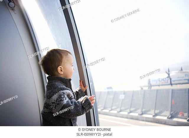 Boy looking through airport window