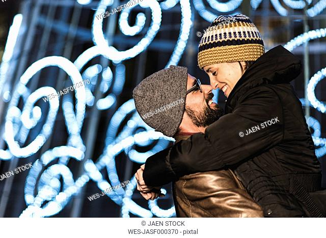 Couple hugging with night lights background