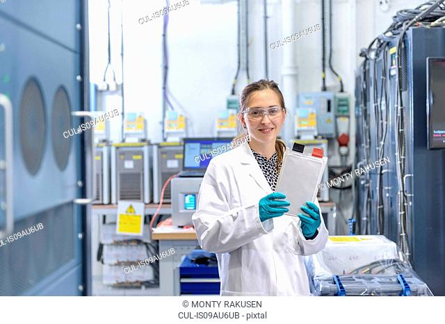 Portrait of female scientist holding lithium ion pouch battery in battery research facility