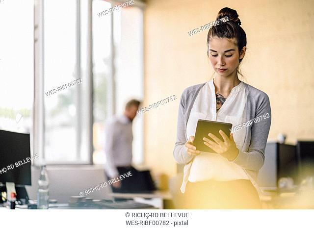Young woman working in office, using tablet