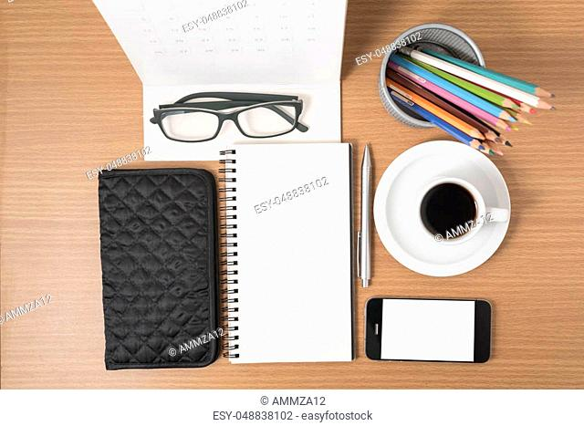 office desk: coffee with phone, wallet, calendar, heart, notepad, eyeglasses, color pencil box on wood background vintage style