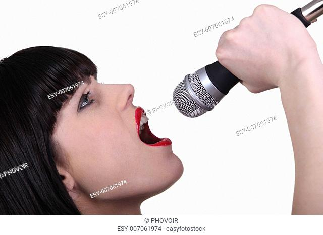 Stunning woman singing into a microphone