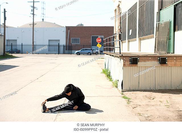 Man stretching in urban environment