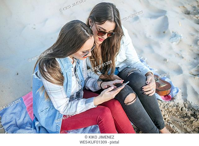 Two young women sitting on the beach looking at cell phone