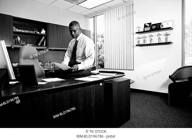 African American businessman sitting on desk