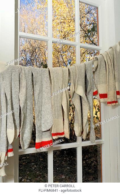 Wool socks hanging on a clothes line by a cottage window, Edmonton, Alberta