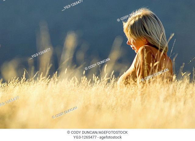 Blond female sitting in golden autumn grass in Arthur's Pass, New Zealand