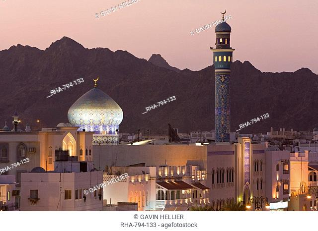 Elevated dusk view of buildings along the Corniche, latticed buildings and Mutrah Mosque, Muscat, Oman, Middle East