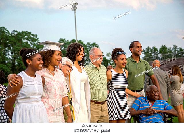 Teenage girl with large family at graduation ceremony