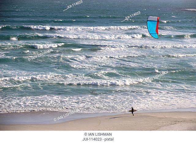 Kiteboarder carrying kiteboard along sunny windy ocean