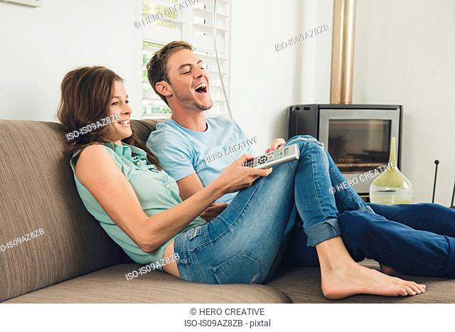 Couple on sofa using remote control laughing