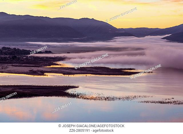 Fog moving over Lake Henshaw during sunrise. San Diego County, California, USA
