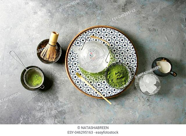 Ingredients for making matcha ice drink. Green tea matcha powder in ceramic bowl, traditional bamboo spoon, whisk on plate, glass teapot