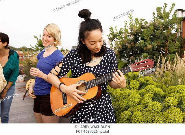 Young woman playing guitar on patio while female friends standing in background