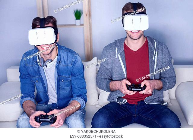 Young men are playing video games at home. They are wearing virtual reality device and smiling. The guys are sitting on sofa