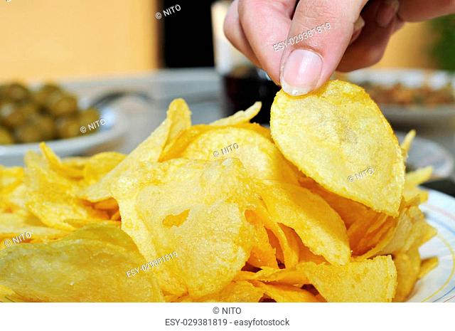 a woman hand picking a potato chips from a bowl on a table with other appetizers, such as pitted olives