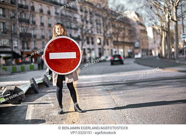 young Asian woman holding no entry traffic sign at street, in Paris, France