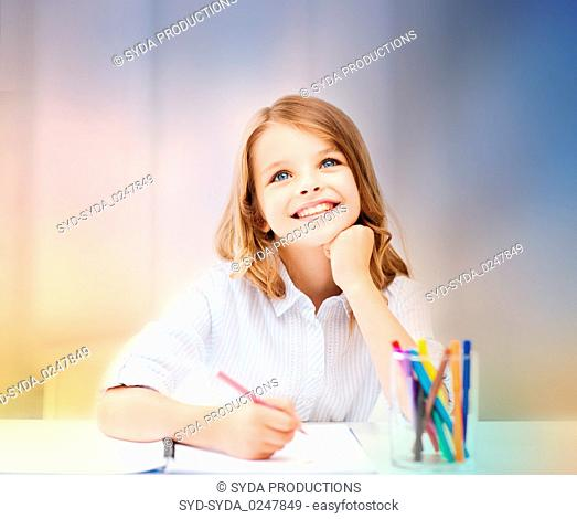 smiling little student girl drawing at school