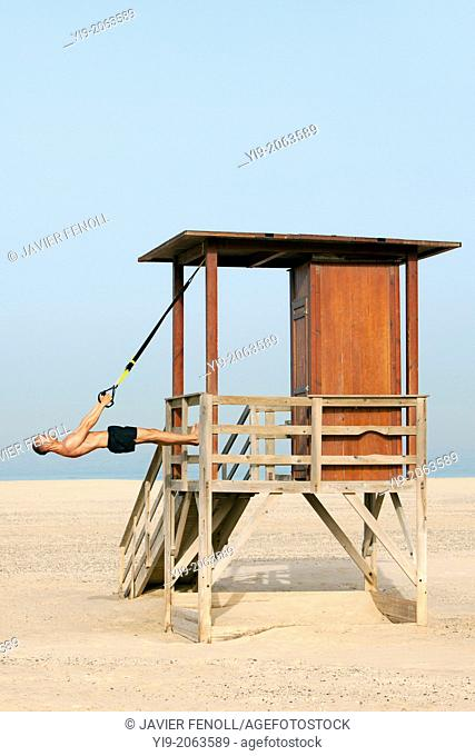 man playing sports on the beach with trx