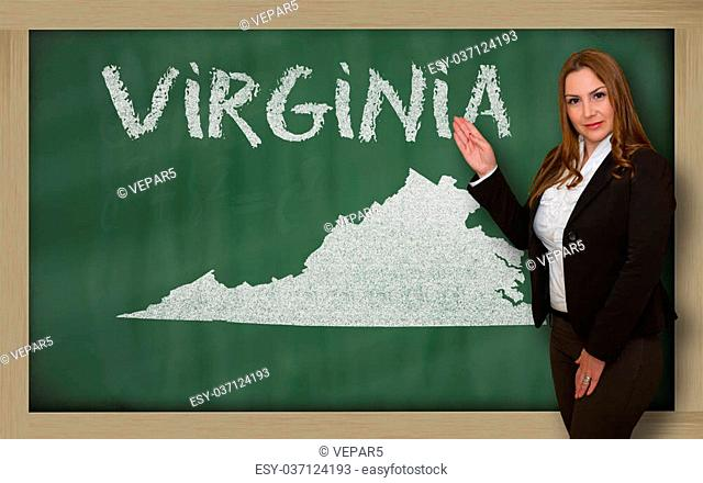 Successful, beautiful and confident young woman showing map of virginia on blackboard for presentation, marketing research and tourist advertising