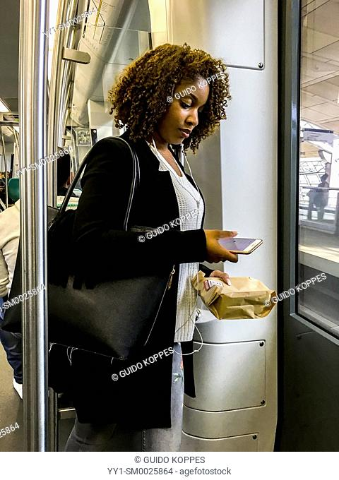 Rotterdam, Netherlands. Young woman totally occupied with her smartphone, while commuting by subway