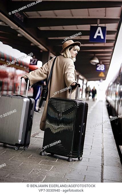 Fashion blogger Esra Eren aka @nachgestern at platform with trolley bags. At Munich central station, Germany