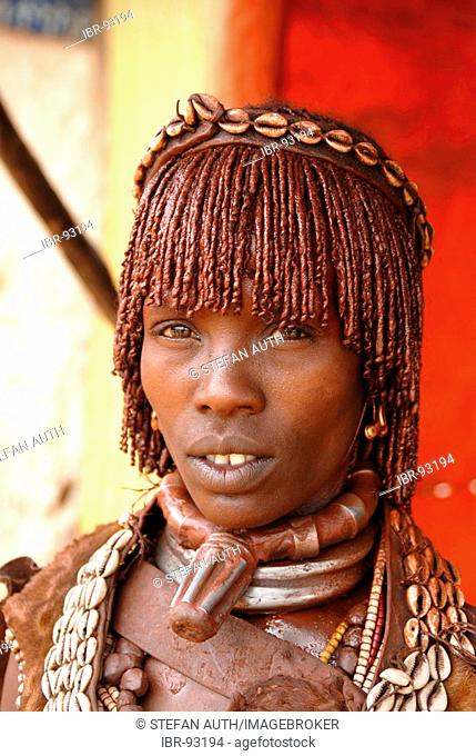 Portrait woman of the Hamar people wears a typical clay hairdo and metal and kauri mussel chains at the market of Dimeka Ethiopia