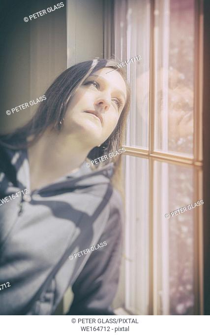 Young woman leaning against a window