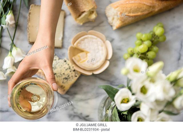 Hispanic woman drinking wine with cheese