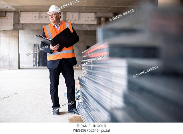 Man with documents wearing safety vest in building under construction
