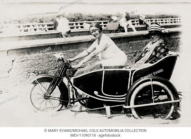 Two ladies posing for photograph on an AJS motorcycle & sidecar combination on the beach at the seaside circa 1914/18