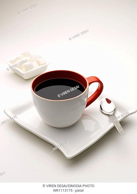 mug of black tea in serving plate with sugar cubes India