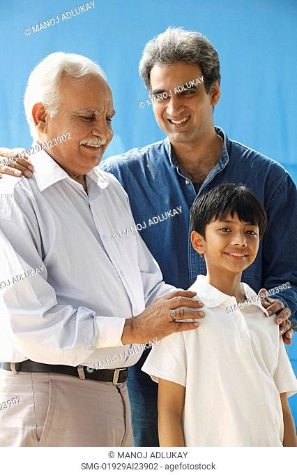 Grandfather, father & son, grandfather with hands on grandson's shoulders