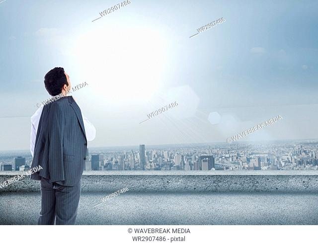 Businessman looking up at sky in city