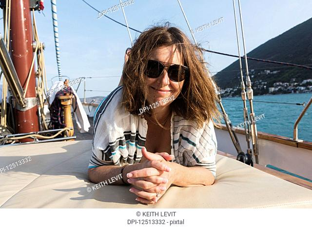 A woman lays on a the deck of a sailboat with windswept hair looking at the camera on the coast of Montenegro; Montenegro