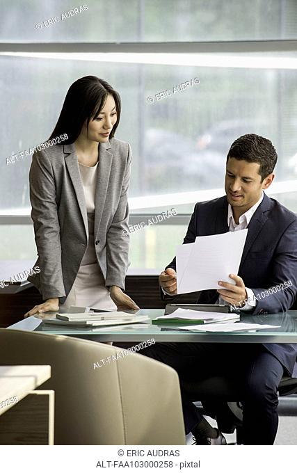 Manager reviewing document with assistant