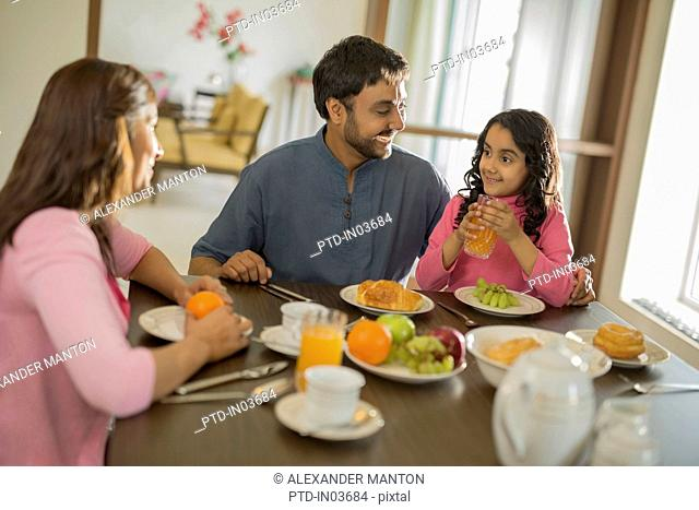 Young girl with orange juice at table with Mother and Father