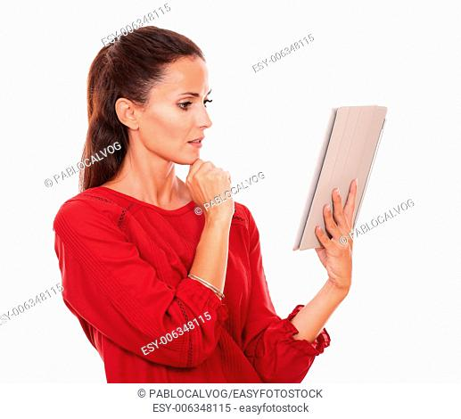 Portrait of pensive young woman on red shirt looking at her tablet pc while standing on isolated studio
