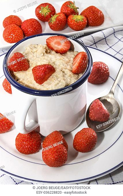 warm porridge in a cup with sweet strawberries