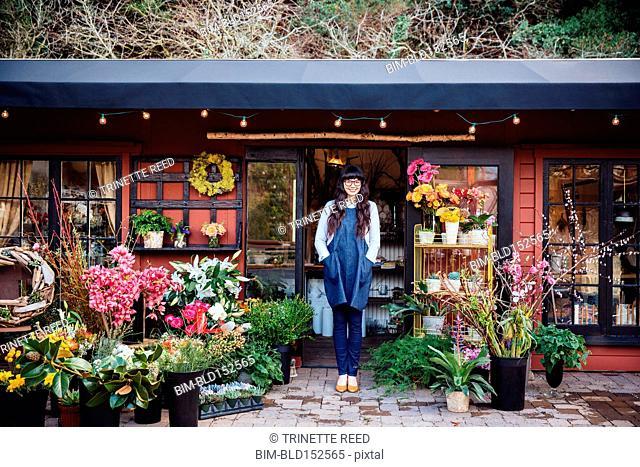 Mixed race florist smiling outside shop