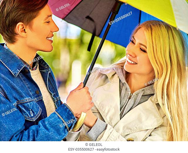 Happy young couple embracing under umbrella in autumn day