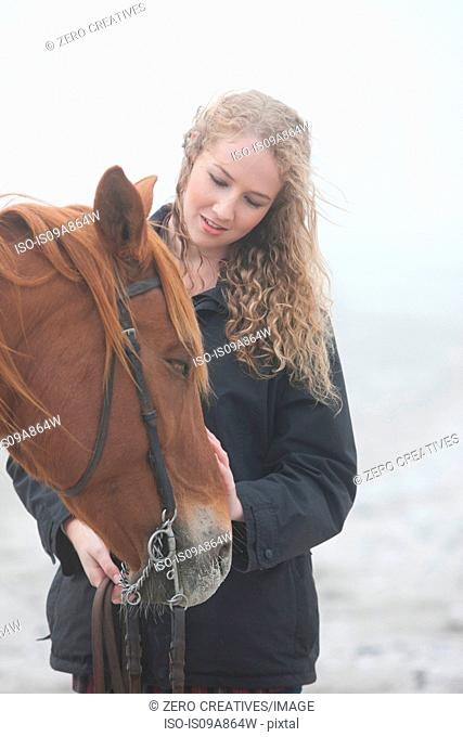 Woman with horse on beach