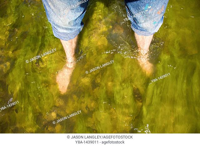 A person's feet in the waters of the Rio Grande River in Big Bend National Park  Standing on the International Border between United States and Mexico
