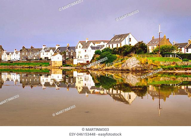View of Port Ellen town houses with water reflection on Isle of Islay, Scotland, United Kingdom