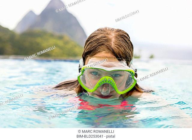 Caucasian girl wearing snorkel mask in swimming pool