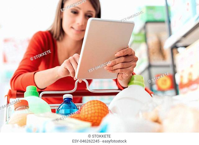Attractive woman shopping at the store and using apps on her digital tablet, technology and consumerism concept